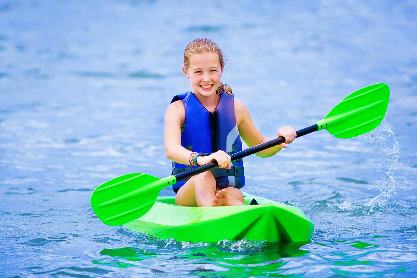 Young girl kayaking in clear water