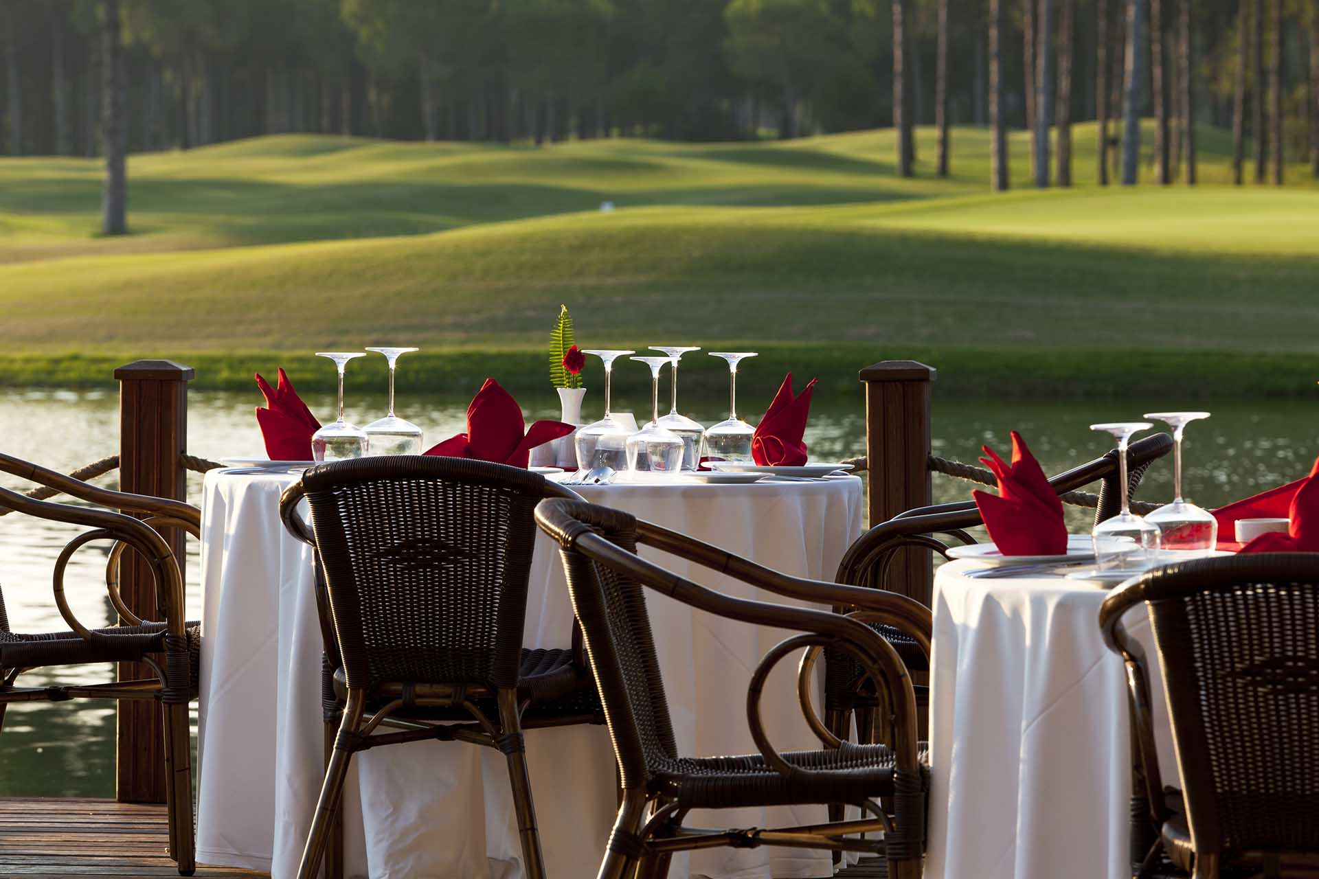 White linen tables overlooking a golf course