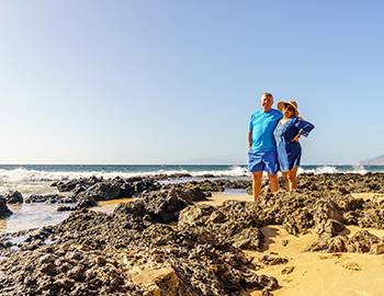 Couple posing by rocks in Maui