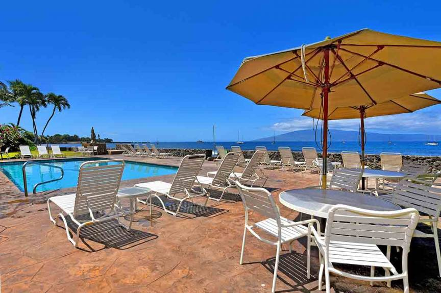 Lounge chairs, umbrellas and a pool at Lahaina Roads Resort